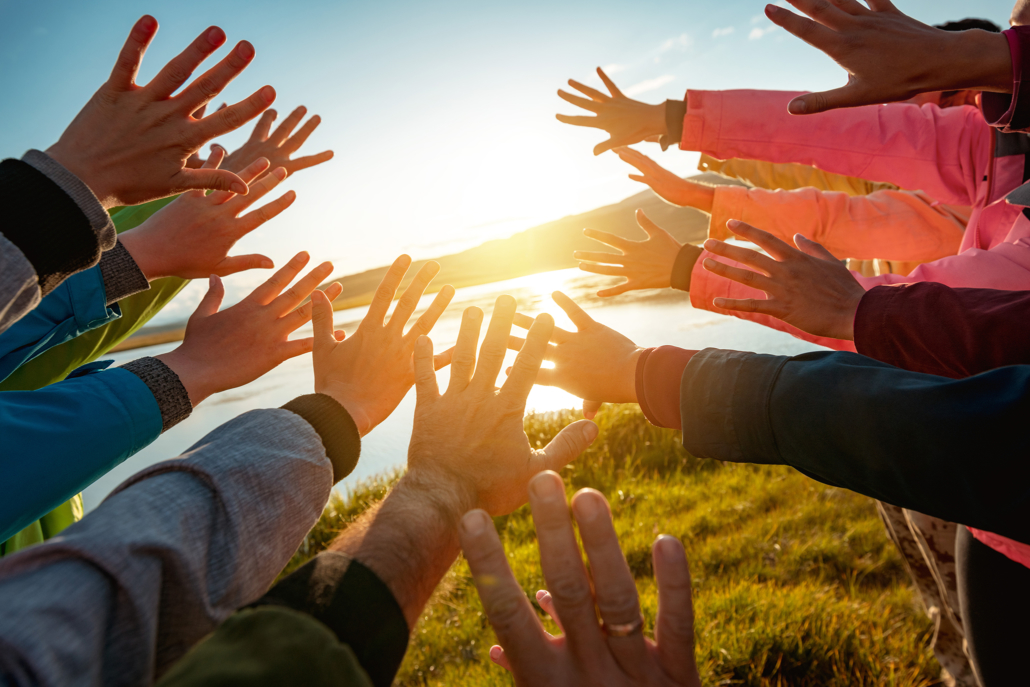 Hands of many friends reaching together for the sun.